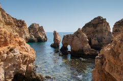 Algarve coast, Portugal. Rocks in the shoreline and blue water Royalty Free Stock Image