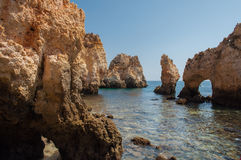 Algarve coast, Portugal. Rocks in the shoreline and blue water Stock Photos