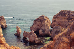 Algarve coast, Portugal. Rocks in the shoreline and blue water Royalty Free Stock Images