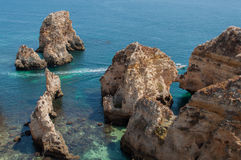 Algarve coast, Portugal. Rocks in the shoreline and blue water Stock Photography