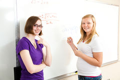 Algebra Class - Teen Girls. Teenage school girls at the board solving algebra problems royalty free stock image