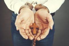 Algemas da mão do homem com cruz imagem de stock