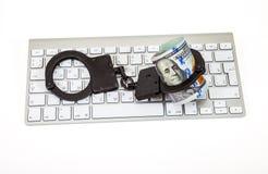 Algemas do aço e dólares de conta que encontra-se em um teclado de computador sobre Fotografia de Stock Royalty Free