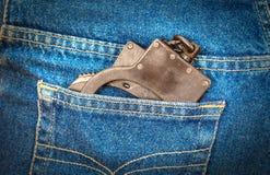 Algemas do metal no bolso traseiro das calças de brim Foto de Stock