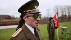 Algemeen in grappige kleren gilt iets in de richting van de militairen stock video