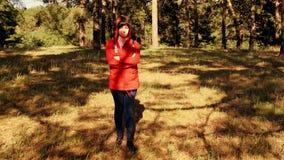 Algemeen overzicht van een jonge vrouw in het hout bij zonsondergang Een meisje in de verse lucht in het bos, de stralen van de z stock videobeelden
