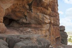 Algemene mening, Badami-Holen, Karnataka Onvolledig hol op de linkerzijde, en toeristen die in hol 2 hieronder binnengaan stock foto's