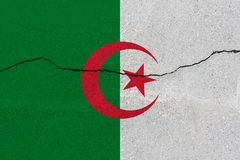 Algeria flag on concrete wall with crack. Patriotic grunge background. National flag of Algeria stock photos