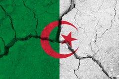 Algeria flag on the cracked earth. National flag of Algeria. Earthquake or drought concept royalty free stock photos