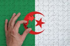 Algeria flag is depicted on a puzzle, which the man`s hand completes to fold.  stock photography