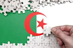 Algeria flag is depicted on a table on which the human hand folds a puzzle of white color.  royalty free stock photos