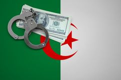 Algeria flag with handcuffs and a bundle of dollars. The concept of breaking the law and thieves crimes.  stock photo