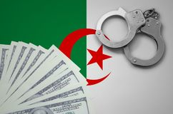 Algeria flag with handcuffs and a bundle of dollars. The concept of illegal banking operations in US currency.  stock photo