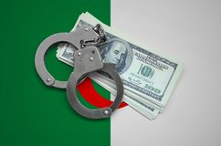 Algeria flag with handcuffs and a bundle of dollars. Currency corruption in the country. Financial crimes.  royalty free stock photos