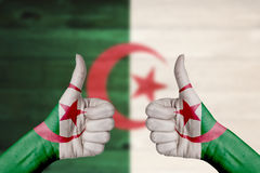 Algeria flag painted on female hands thumbs up. With blurry wooden background Stock Photo