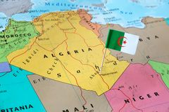 Algeria flag pin on map. Algeria paper flag pin on a country map. Officially the People`s Democratic Republic of Algeria is a sovereign state in North Africa on royalty free stock images