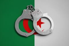 Algeria flag and police handcuffs. The concept of observance of the law in the country and protection from crime.  royalty free stock photos