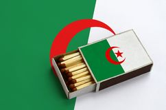 Algeria flag is shown in an open matchbox, which is filled with matches and lies on a large flag.  stock photography