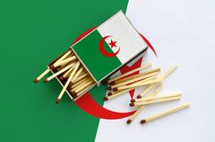 Algeria flag is shown on an open matchbox, from which several matches fall and lies on a large flag.  royalty free stock images