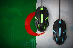 Algeria flag and two mice with backlight. Online cooperative games. Cyber sport team. Algeria flag and two modern computer mice with backlight. The concept of stock images
