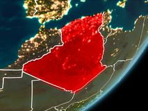 Algeria on night Earth. Algeria as seen from Earth's orbit on planet Earth at night highlighted in red with visible borders and city lights. 3D illustration Stock Photo