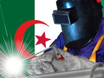 ALGERIA WELDER WITH BACKGROUND OF HIS FLAG. WELDER OF ALGERIA WITH THE BACKGROUND OF HIS FLAG, WORKING THAT GENERATES WELL-BEING AND RICHES TO HIS COUNTRY AND TO stock photography