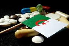 Algerijnse vlag met partij van medische die pillen op zwarte backgr wordt geïsoleerd Stock Foto's