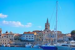 Alghero kyrktorn som ses från hamnen Fotografering för Bildbyråer
