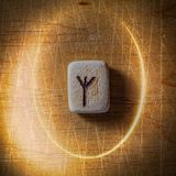 Algiz. Handmade scandinavian wooden runes on a wooden vintage background in a circle of light. Concept of fortune stock photo