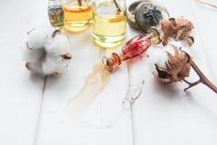 Algodón del perfume y de las flores y orquídea blanca en la tabla de madera blanca Imágenes de archivo libres de regalías