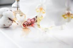 Algodón del perfume y de las flores y orquídea blanca en la tabla de madera blanca Fotos de archivo libres de regalías