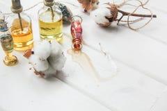 Algodón del perfume y de las flores y orquídea blanca en la tabla de madera blanca Imagenes de archivo