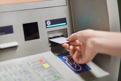 Alguém decola o dinheiro do terminal exterior do banco, introduz o cartão de crédito plástico na máquina do atm, indo retirar o d foto de stock