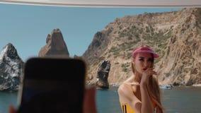 Alguém faz uma foto no telefone de uma menina bonita em um roupa de banho em um iate em uma baía com as rochas no movimento lento vídeos de arquivo