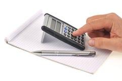 Alguém que usa uma calculadora em um bloco de notas em um fundo branco fotos de stock royalty free