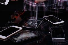 Alguém quebra smartphones diferentes com uma chave de fenda Em um fundo preto Close-up foto de stock