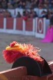 Alguacilillo de chapeau avec les plumes rouges et jaunes sur le burladero dans la corrida, Espagne Photo stock