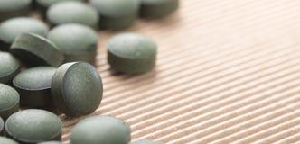 Algues vertes bleues Détail des Tablettes artisanales de Spirulina au-dessus de national Image stock