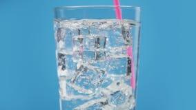 Alguien bebida de la agua fría de la mezcla con el fondo azul chispeante de la soda de la paja de beber metrajes