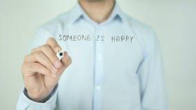 Alguien es feliz con menos que lo que usted tiene, escribiendo en la pantalla transparente almacen de metraje de vídeo