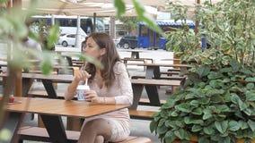 Alguien está mirando a una muchacha que esté comiendo el helado en un café en la calle metrajes