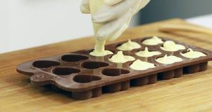 Alguien exprime el chocolate en molde del chocolate