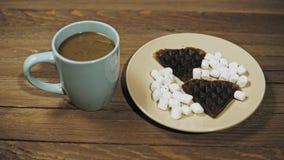 Alguien fija la tabla para el desayuno, el café y las galletas con las melcochas almacen de metraje de vídeo