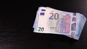 Alguien pone el paquete de 20 billetes de banco de los euros en la tabla negra almacen de metraje de vídeo