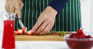 Alguien que usa el cuchillo a cortar las fresas almacen de video