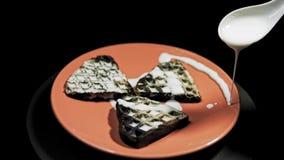 Alguien sirve el desayuno, regando las galletas del corazón de la salsa blanca almacen de metraje de vídeo