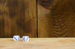 Algum dado encontra-se na superfície da madeira natural Os artigos para gerar numeram de um a seis sob a forma dos pontos que são imagem de stock