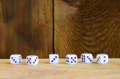 Algum dado encontra-se na superfície da madeira natural Os artigos para gerar numeram de um a seis sob a forma dos pontos que são foto de stock royalty free