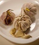 Algum garlics em uma placa Fotos de Stock