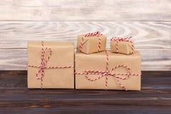Algum papel parcela as caixas de presente do Natal envolvidas com papel kraft e amarradas com guita branca vermelha do padeiro em Fotos de Stock Royalty Free